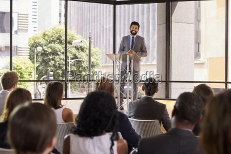 hispanic man presenting business seminar smiling