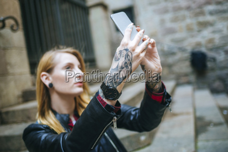 tattooed womans hands taking selfie with
