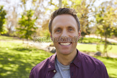 happy white adult man in park