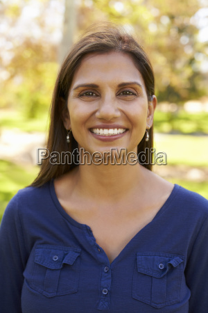 smiling mixed race woman in park