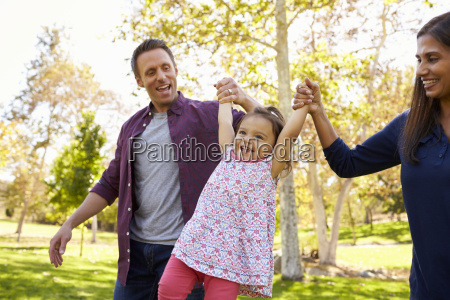 mixed race couple lifting young daughter