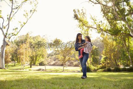 asian caucasian woman carrying her young
