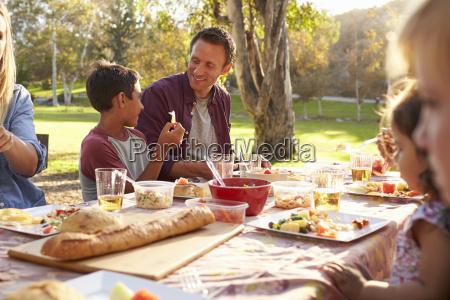 zwei familien die oben ein picknick