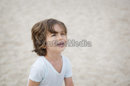 boy on the beach looking up
