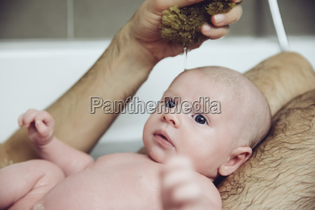 father and baby taking a bath