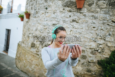 young woman weith headphones taking selfies