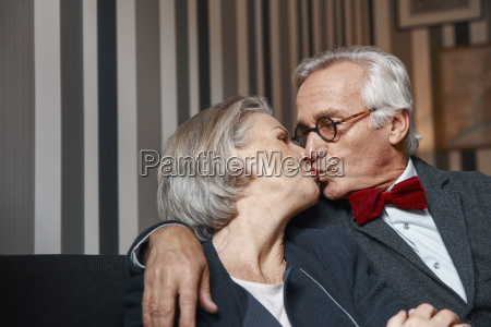 senior couple kissing on couch