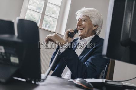 laughing senior businessman on the phone