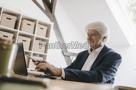 smiling senior businessman using laptop in