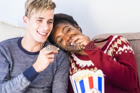 glueckliche junge paar auf der couch
