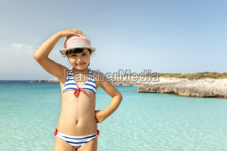 girl standing at the beach smiling