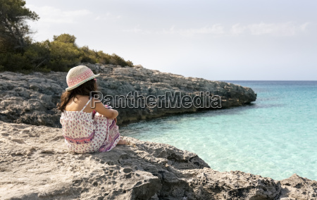 girl sitting at the beach looking