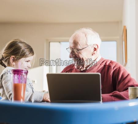 grossvater und enkelin mit laptop zusammen