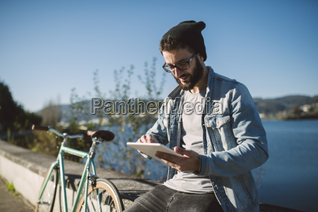 smiling young man using a tablet