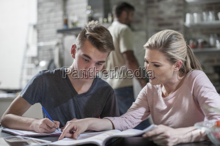 mother helping son with homework while