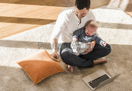 father sitting cross legged with baby