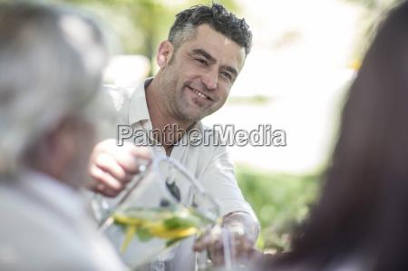 smiling man pouring lemonade into glass