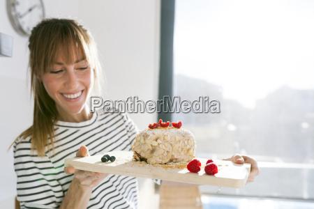 junge frau praesentiert veganen kuchen