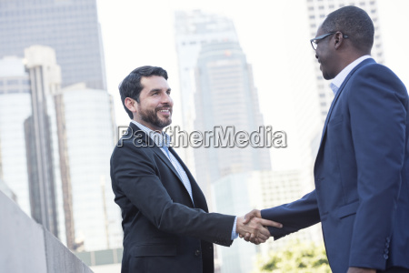 two businessmen shaking hands in the
