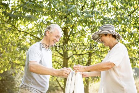 happy senior couple folding blanket in