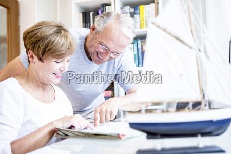 senior couple at desk with magazine