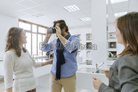 customers consulting saleswoman in shop for