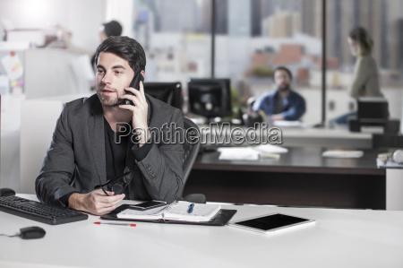 geschaeftsmann auf dem telefon im buero