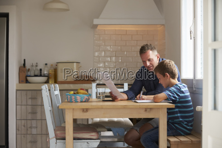 father helping son with homework sitting