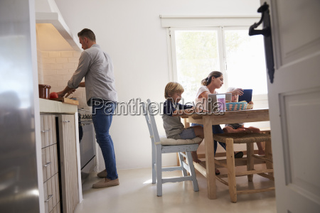 dad cooking and mum with kids