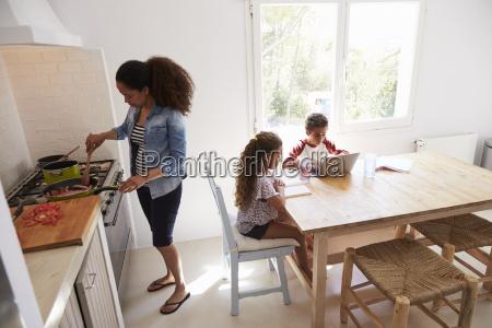 mum cooking while kids work at