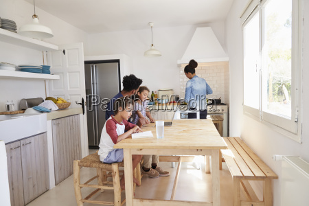 dad sitting with kids at kitchen
