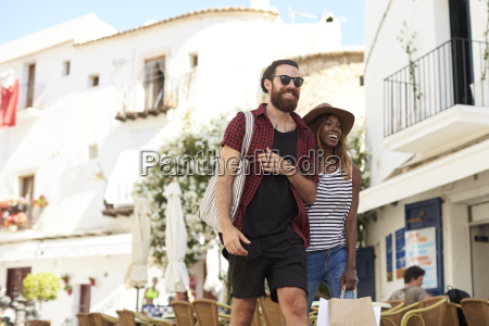 young adult couple on vacation shopping