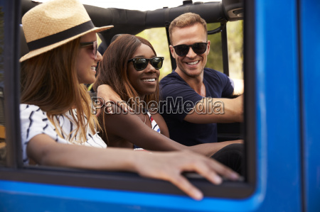 group of friends driving open top