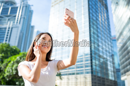 woman using cellphone for taking selfie