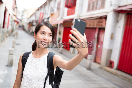 woman using cellphone to take selfie