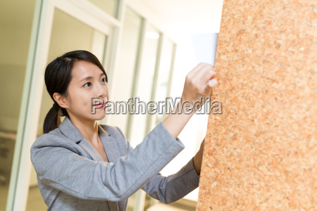 businesswoman posting paper on the wall