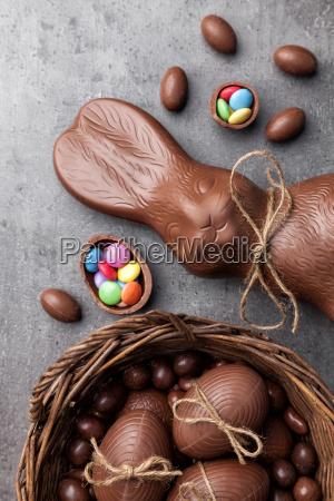 schokoladen osterhase und eier auf holzhintergrund