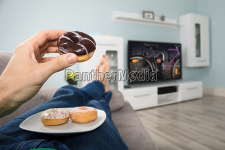person eating donut while watching television