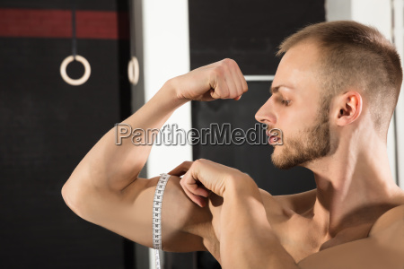 man measuring arm with tape measure