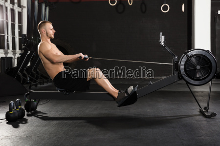 young man exercising with row machine