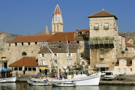 fishing boats in harbour with houses