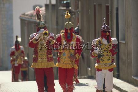 trompetenspieler in roten kostuemen und pferdeschwanzen