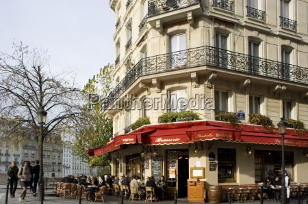 people sitting outside a brasserie on
