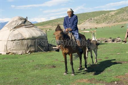 kazak woman on horseback beside a