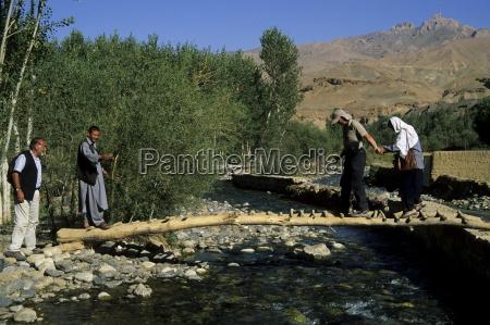 tourists crossing log bridge kakrak valley