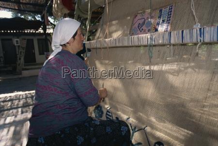 woman weaving wool carpet on a