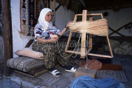 woman gathering dyed wool in carpet