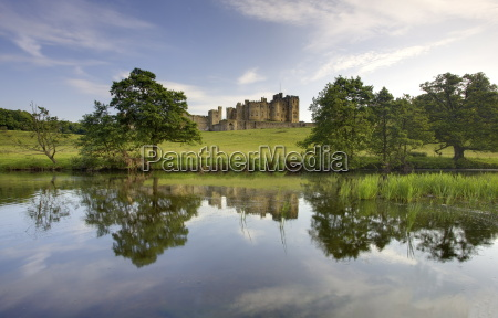 alnwick castle reflecting in river aln