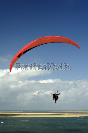 red hang glider over bay of