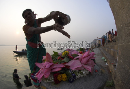 woman pouring water over flowers on
